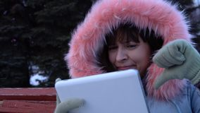 A young woman in a warm jacket uses a digital tablet in the park in the winter. Portrait of a young unhappy woman uses a digital tablet and sitting on a bench stock video