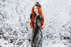 Portrait of young unusual pale girl with long red hair on winter background. Beautiful redhead retro woman in black dress and with. Long gloves on a background stock images