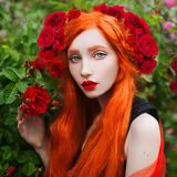 Portrait of young unusual pale girl with red hair in rose garden. Beautiful redhead woman with hairdo from roses. Pale skin. Expressive look stock image