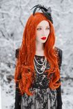 Portrait of young unusual pale girl with red hair on winter background. royalty free stock photos