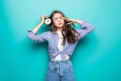Portrait of young upset puzzled woman student in denim clothes hold alarm clock isolated on blue background. Time is running out. Education in university stock photos