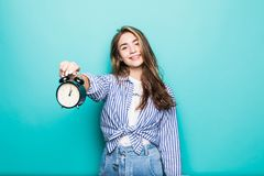 Portrait of young smile puzzled woman student in denim clothes hold alarm clock isolated on blue background. Time is running out. Portrait of young upset stock images