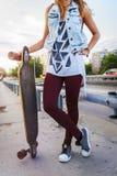 Skateboarding girl standing in the street holding long-board skateboard Royalty Free Stock Photo