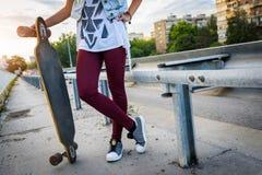 Skateboarding girl standing in the street holding long-board skateboard Stock Image