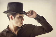 Portrait of a Young Vampire Man with Black Shirt and Top Hat. Tipping his Hat, looking to right Royalty Free Stock Images