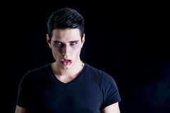 Portrait of a Young Vampire Man with Black T-Shirt. Looking at the Camera, on a Dark Smoky Background Stock Photos