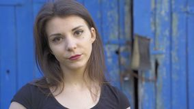 Portrait of a young village woman with dark brown hair and a black T-shirt, shot in the countryside. Close-up stock video footage