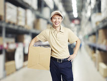 Portrait of a young warehouse worker carrying a carton box Royalty Free Stock Photography