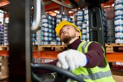 Mover Using Forklift in warehouse. Portrait of young warehouse worker sitting inside forklift moving goods from tall storage shelves and looking up, copy space Royalty Free Stock Photos
