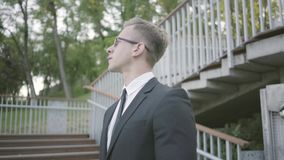 Portrait of young well-dressed businessman standing in the park looking away. The office manager waiting for client. Portrait of young well-dressed businessman stock video