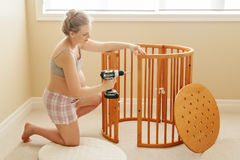 Portrait of young white Caucasian happy woman assembling wooden baby crib in nursery at home Royalty Free Stock Image