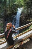 Portrait of a young white Caucasian male tourist in sportswear and glasses making a photo of waterfall royalty free stock photos