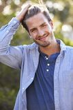 Portrait of young white man with hand in hair outdoors Royalty Free Stock Images