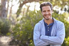 Portrait of young white man smiling arms crossed outdoors Royalty Free Stock Image