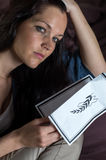 Portrait of young widow holding obituary Stock Photo