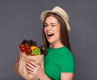 Young winking woman holding paper bag with vegetables. Royalty Free Stock Image