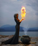 Portrait of a young witch creating a burning skull. 3D rendering of a young witch creating a magical skull out of flames Stock Image