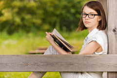 Portrait of young witty woman. Portrait of young attractive earnest brunette woman wearing white clothes, reading book, sitting at summer green park Royalty Free Stock Images