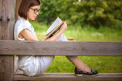 Portrait of young witty woman with book. Portrait of young attractive earnest brunette woman wearing white clothes, reading book, sitting at summer green park Royalty Free Stock Photos