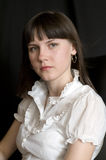Portrait of a young woman. Young woman in a white blouse wearily looks ahead Royalty Free Stock Photos