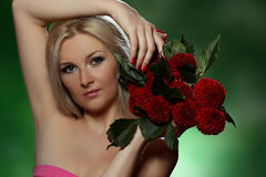 Portrait of a young woman. With red flowers on green background Royalty Free Stock Image