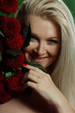Portrait of a young woman. With red flowers on green background Royalty Free Stock Images