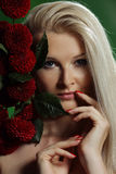 Portrait of a young woman. With red flowers on green background Royalty Free Stock Photo