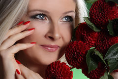 Portrait of a young woman. With red flowers on green background Stock Image