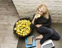 Portrait of young woman. With a laptop next to the basket of apples Stock Photo