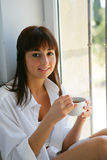 Portrait of a young woman. Young woman drinking a cup of coffee at home Stock Image