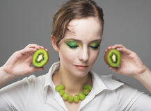 Portrait of young woman. With  pieces of kiwi Stock Photography