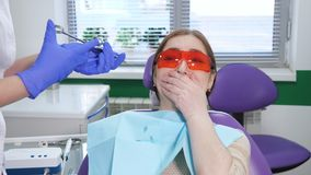 Portrait of young woman afraid to remove a tooth sitting in dental chair. While the doctor stands next to the patient stock video footage