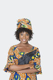 Portrait of young woman in African print attire standing arms crossed over gray background Stock Images