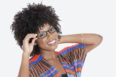 Portrait of young woman in African print attire wearing glasses over gray background Royalty Free Stock Photography
