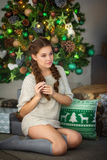 Portrait of the young woman against the background of a Christmas tree Stock Image