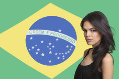 Portrait of young woman against Brazilian flag Stock Photography