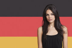 Portrait of young woman against German flag Stock Photography