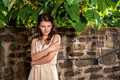 Portrait of young woman against old stone wall Stock Photo