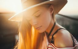 Portrait of young woman against of sunset background. royalty free stock images