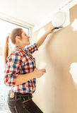 Portrait of young woman aligning gypsum cardboard Stock Photo