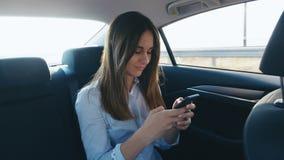 Portrait Young Woman använder sin smartphone under resan i en bil med en drivrutin Flickan kollar e-post, chatt medan lager videofilmer