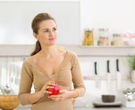 Portrait of young woman with apple in kitchen Stock Image