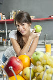 Portrait of young woman with apple in kitchen stock images