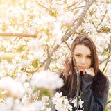 Portrait young woman in apple trees blooming park on a sunny day. Dark hair. Happiness concept.