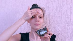 Woman is applying fresh homemade coconut mask on the face from coconut shell. Portrait of young woman is applying fresh homemade coconut mask on the face from stock video footage