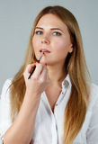 Portrait of young woman applying lips make up Royalty Free Stock Photo