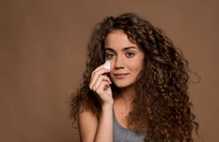 Portrait of a young woman applying make-up in a studio against brown background. A portrait of a young woman applying make-up in a studio against brown stock photography