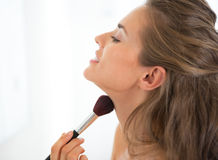 Portrait of young woman applying makeup Stock Photo