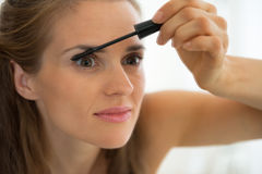 Portrait of young woman applying mascara Stock Image