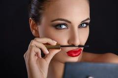 Portrait of young woman applying mascara.  Mascara Brush. Red Li Stock Photography